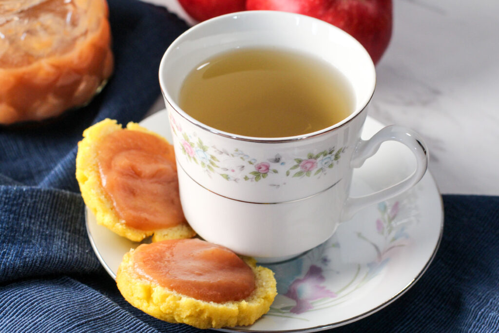 teacup filled with tea and biscuits sitting on teacup plate