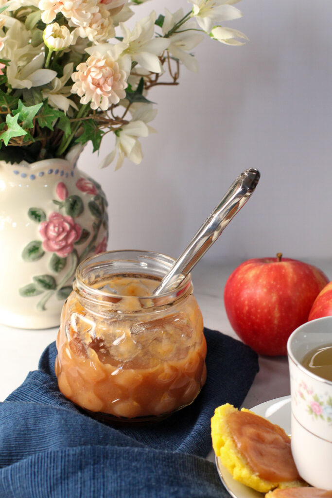 half filled jar of apple butter with knife in it