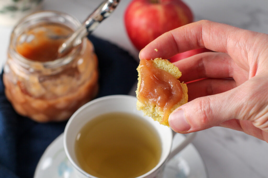 hand holding mostly eaten biscuit with apple butter