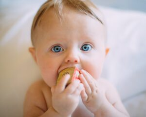 Baby with wood block in mouth
