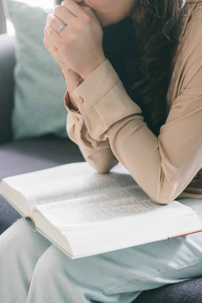 woman with hands folded praying with Bible in lap