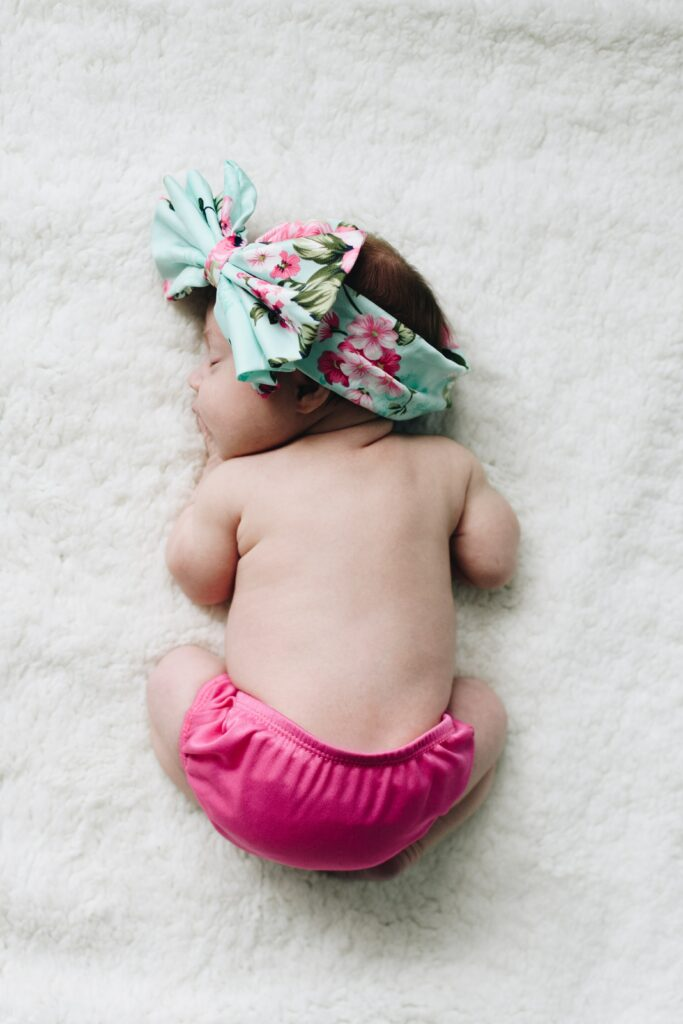 Baby sleeping curled up on the ground with bright pink diaper and large headband