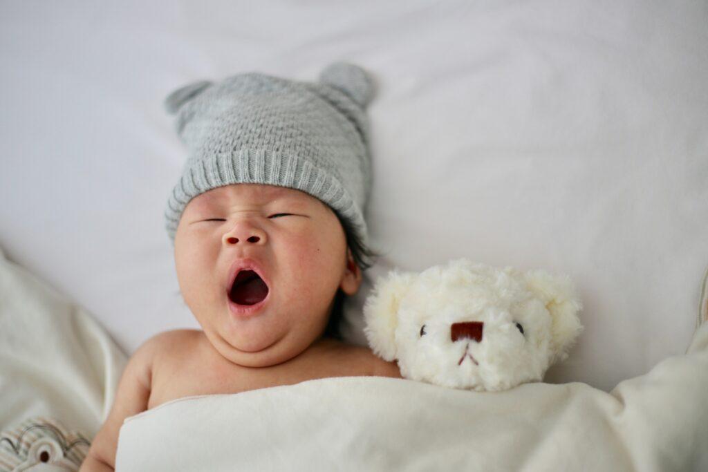 Baby yawning laying next to stuffed animal