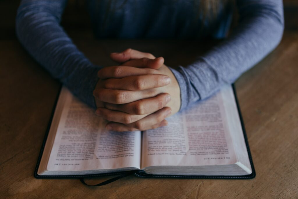 hands folded in prayer on Bible