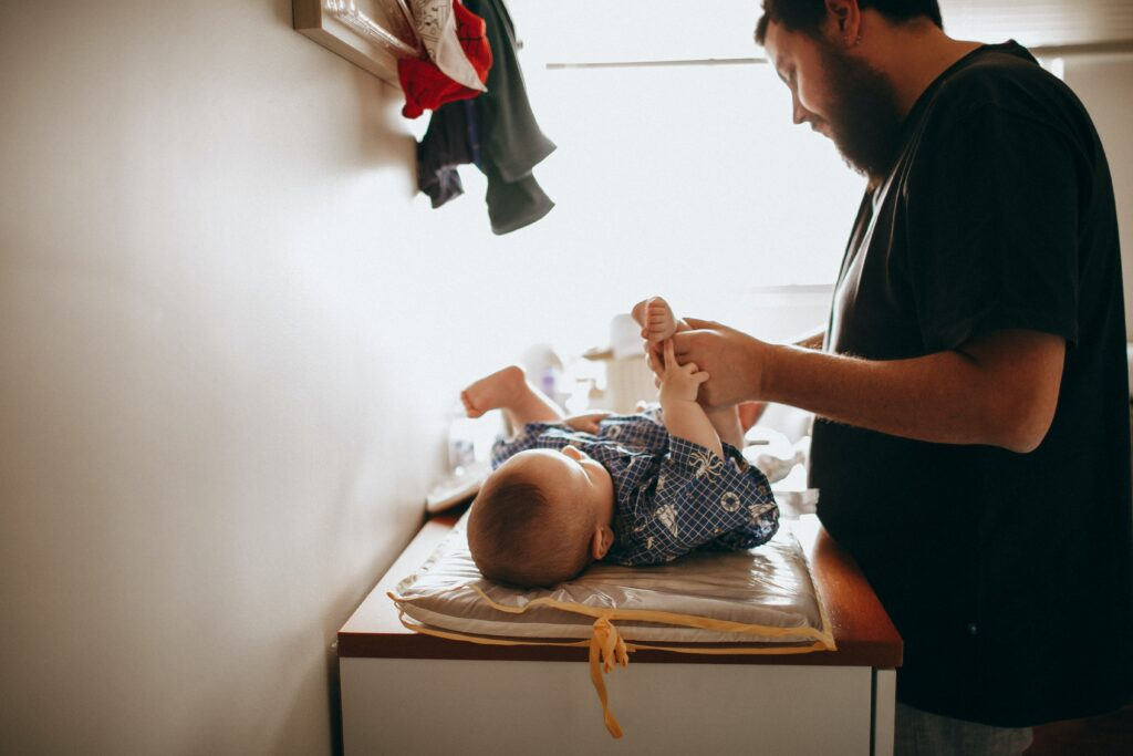 dad changing baby's diaper on changing table