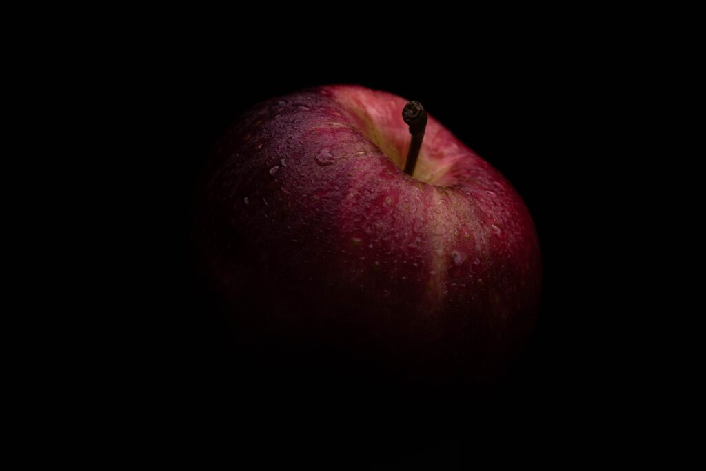 black background with red apple half showing