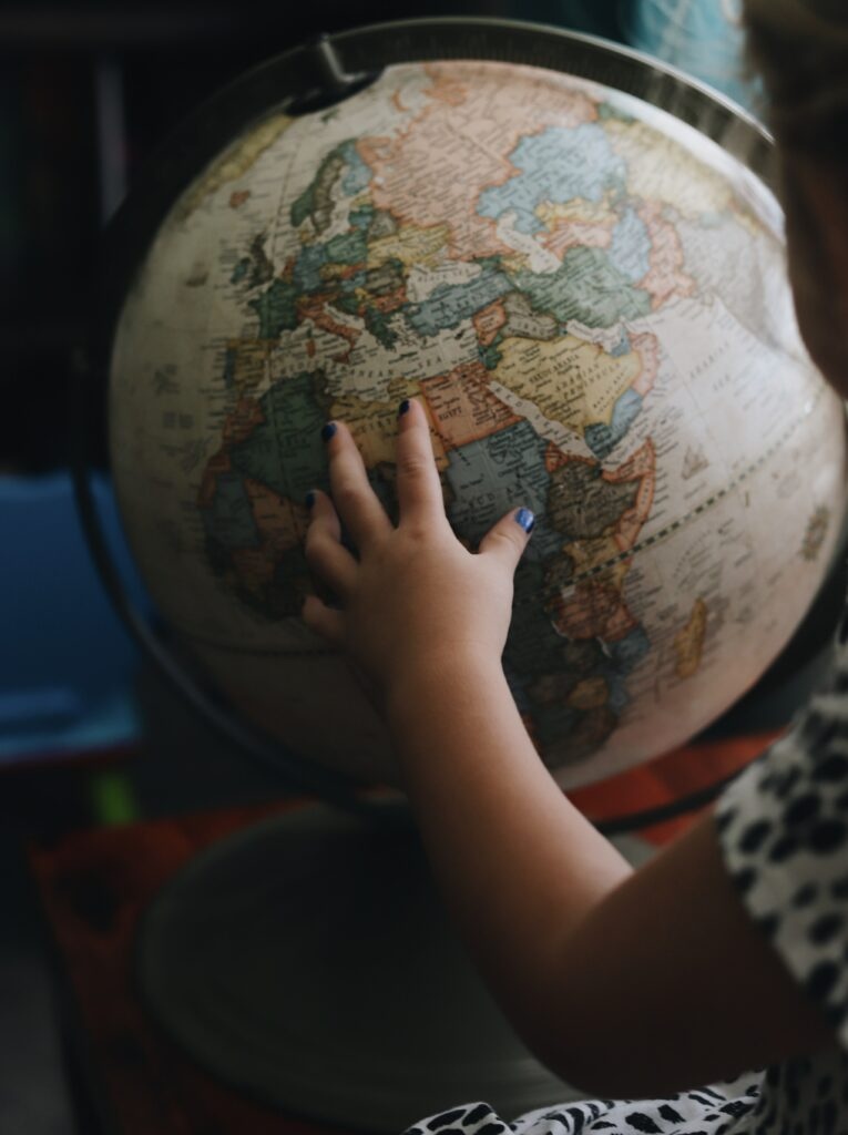 little girls hand on globe