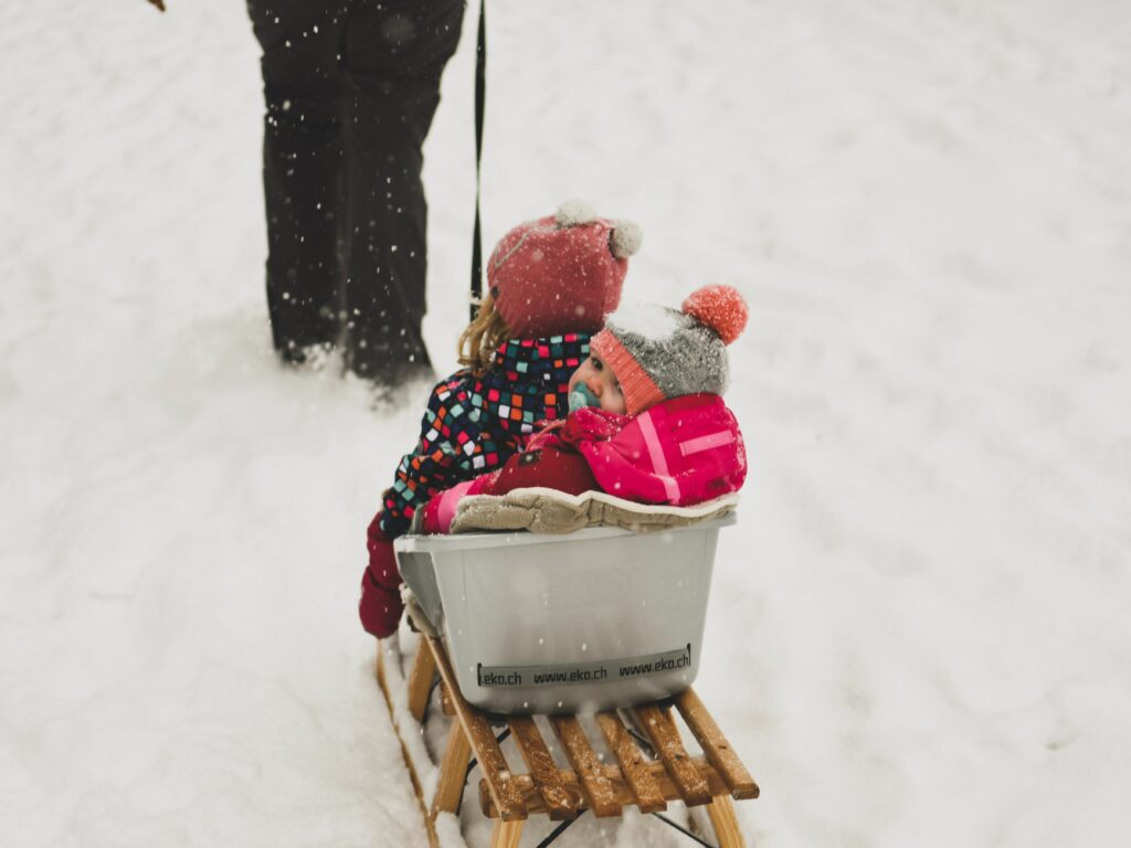 kids riding in sled with someone pulling them up the hill