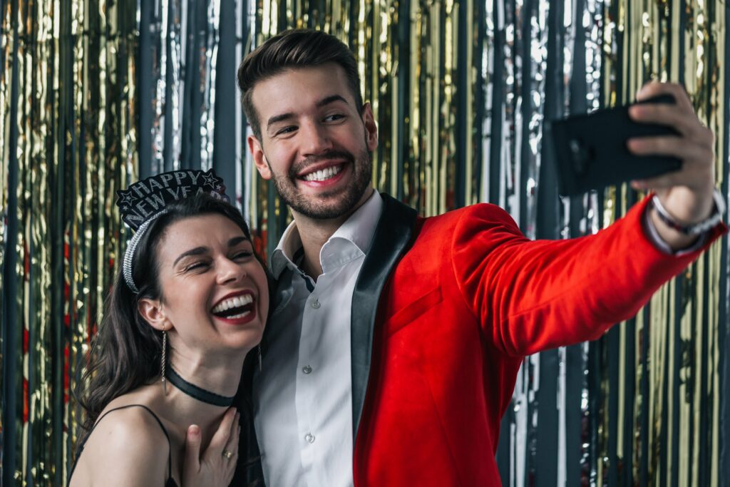 couple taking a new years eve selfie in a home made photo booth