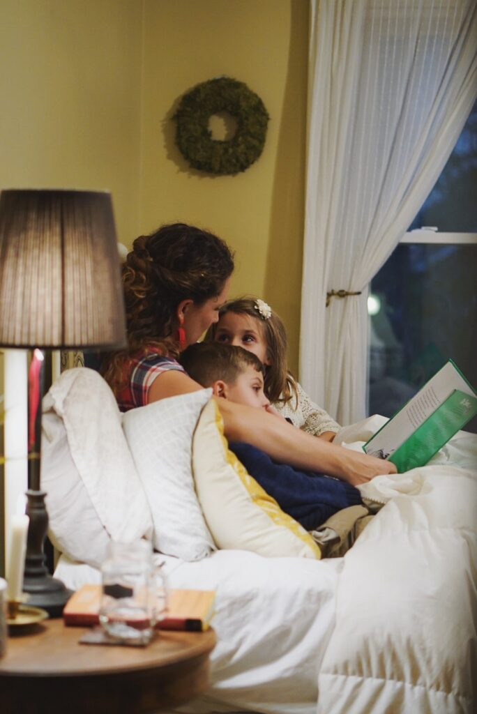 mom reading a book to two kids in bed