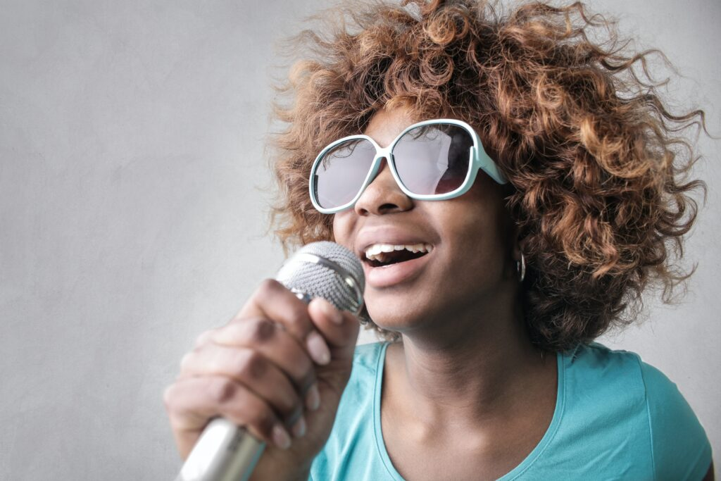 lady with sunglasses holding microphone singing