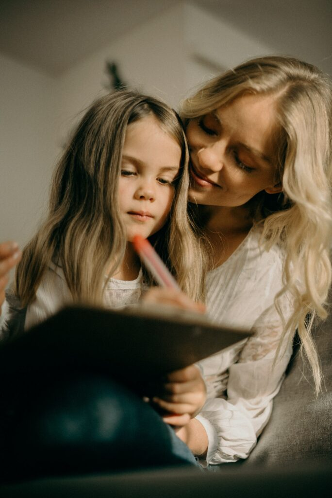 Little girl writing on clipboard with mom next to her as a New Years Eve at Home idea to write a family bucket list