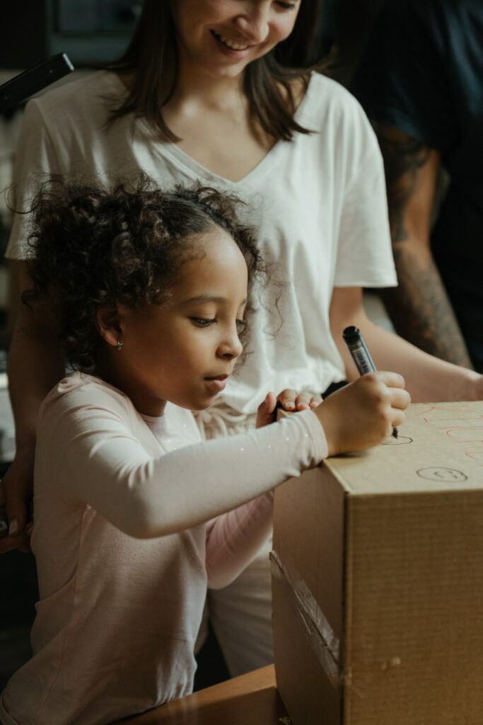 little girl writing on box