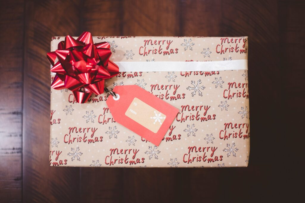 gift wrapped in Merry Christmas paper with red bow and tag