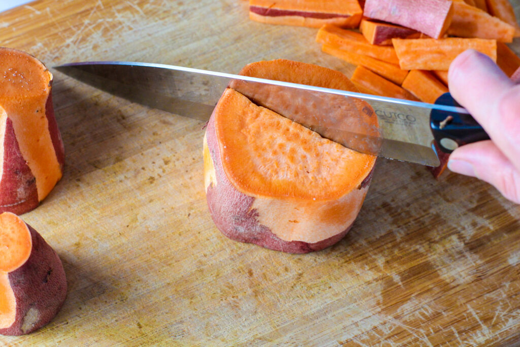 knife cutting a sweet potato piece in half