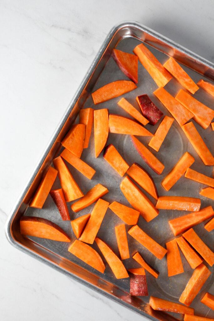 raw sweet potato fries on baking sheet