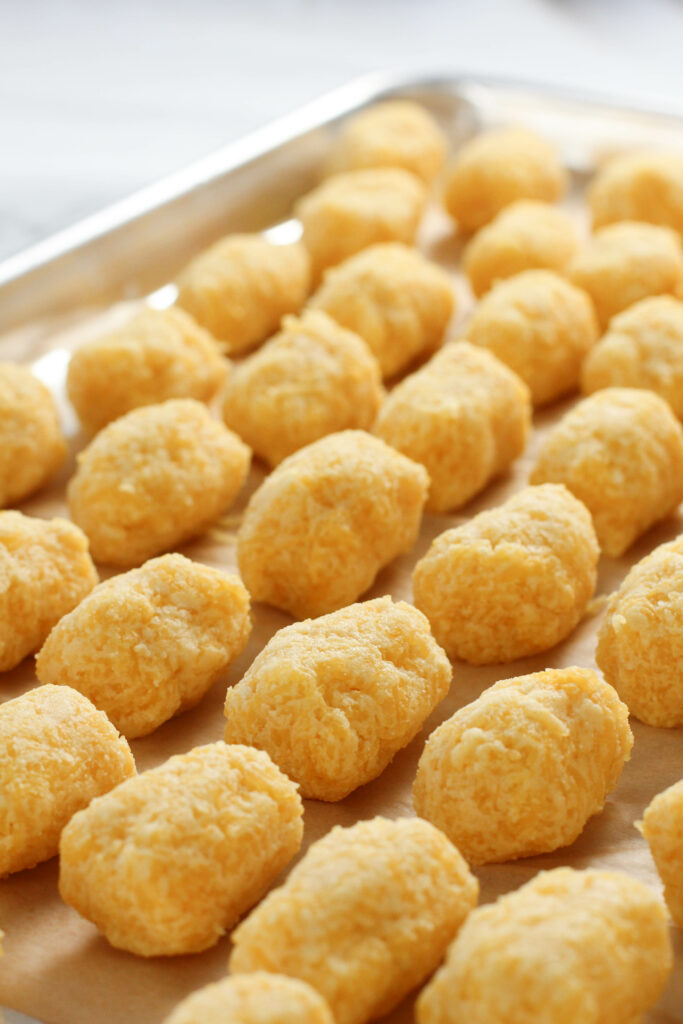 Baking sheet with rows of spaghetti squash tater tots