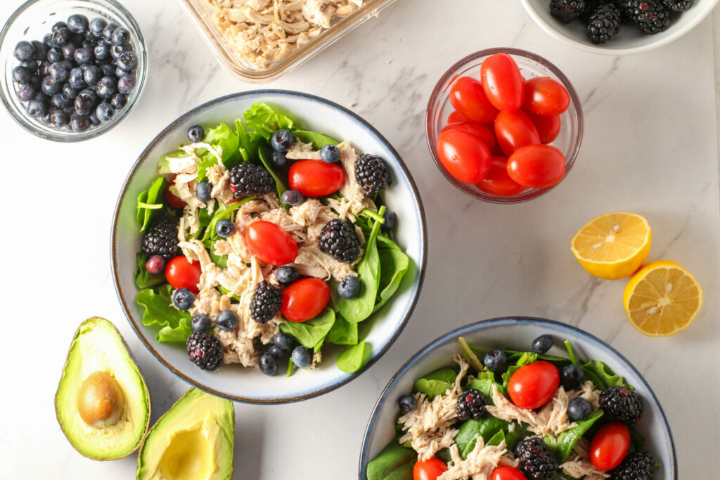 two bowls of green salad surrounded by ingredients