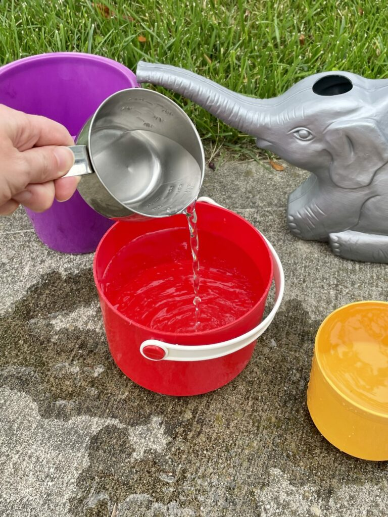 hand pouring water into red bucket for easy backyard summer activities