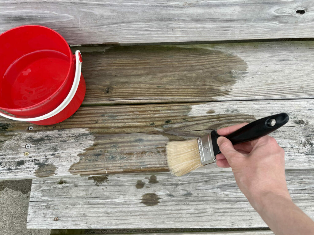 hand using paint brush and water on wood patio for easy backyard summer activities