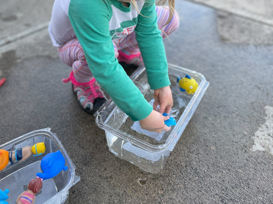child playing with water toys in plastic bin for easy backyard water activities
