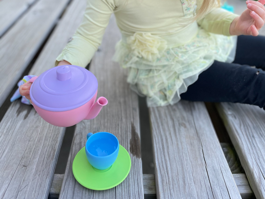 child's hand holding teapot for easy backyard water activities
