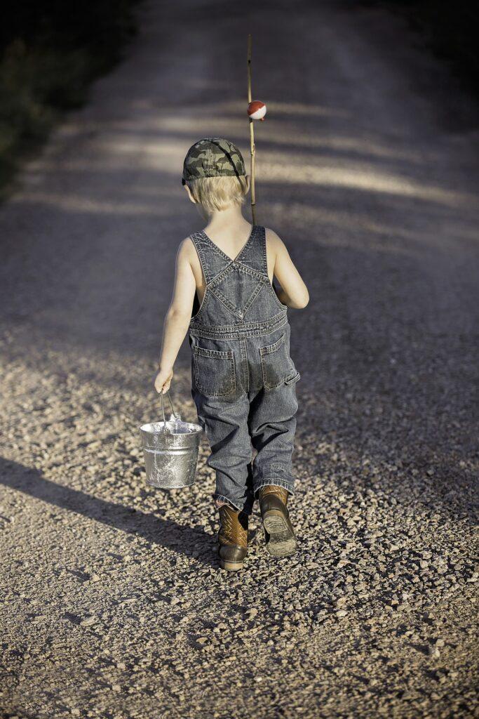 boy walking with fishing pole
