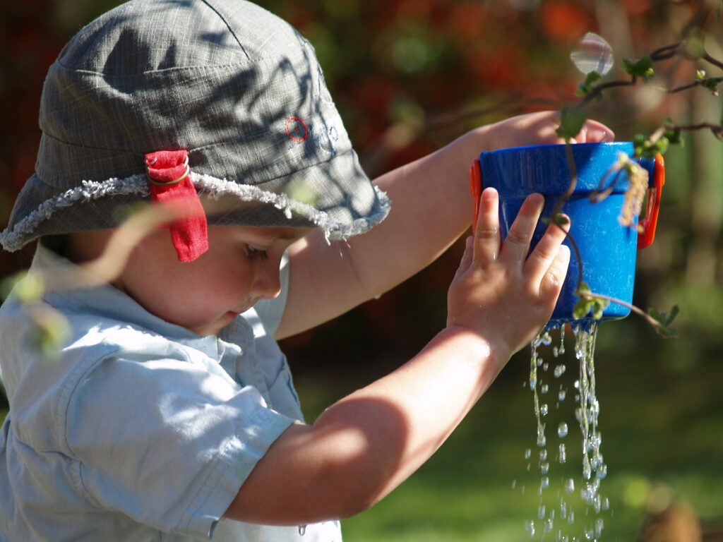 little boy holding up toy with water dripping out of the bottom