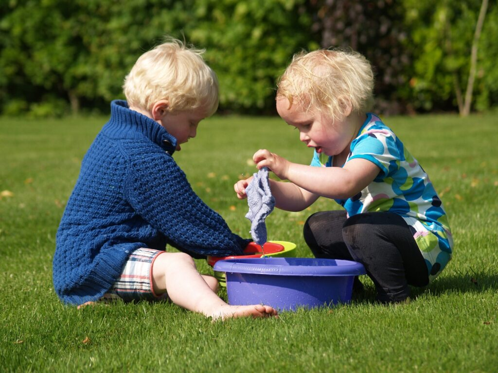 two kids playing with wash cloth and buckets of water