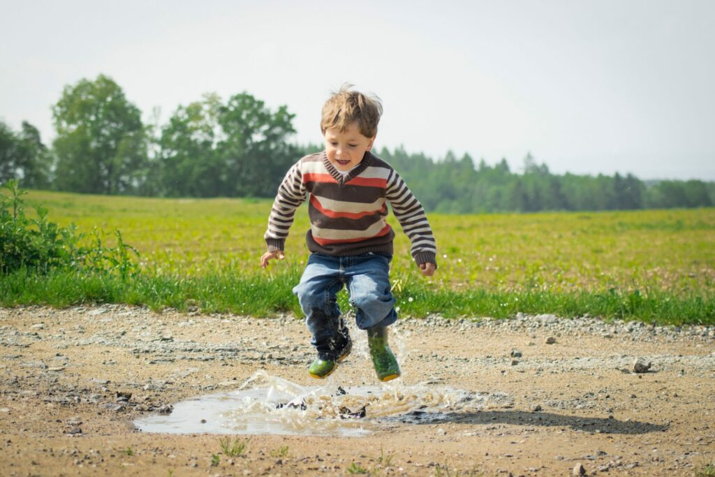 kid stomping in rain puddle