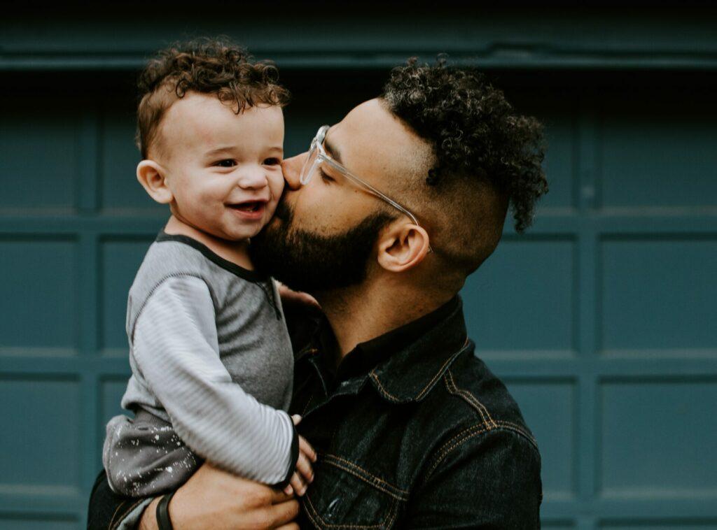dad kissing sons check