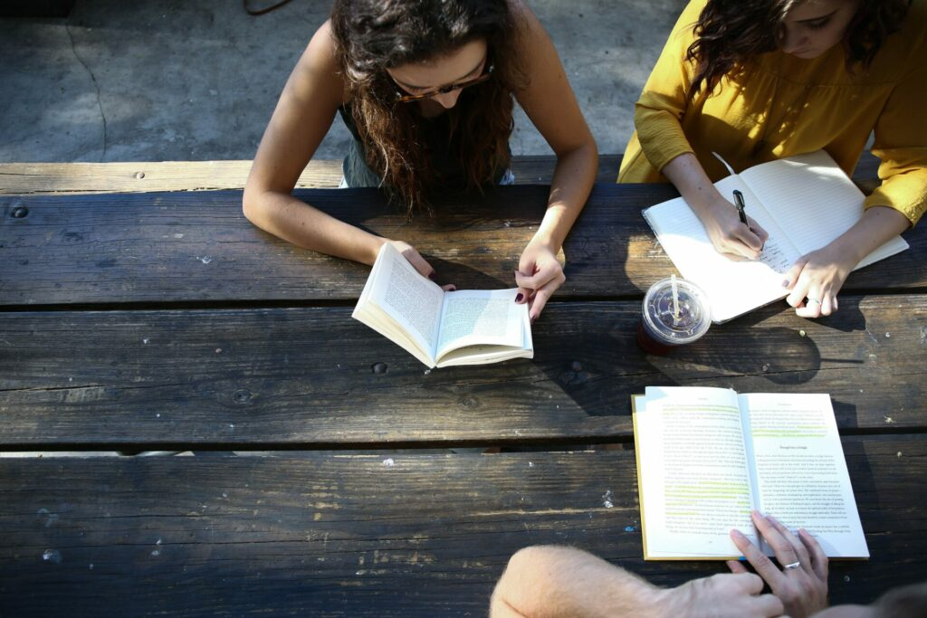 three people sitting at wooden table reading books and taking notes