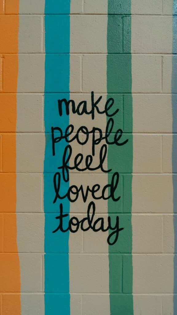 wall with striped paint that says make people feel loved today
