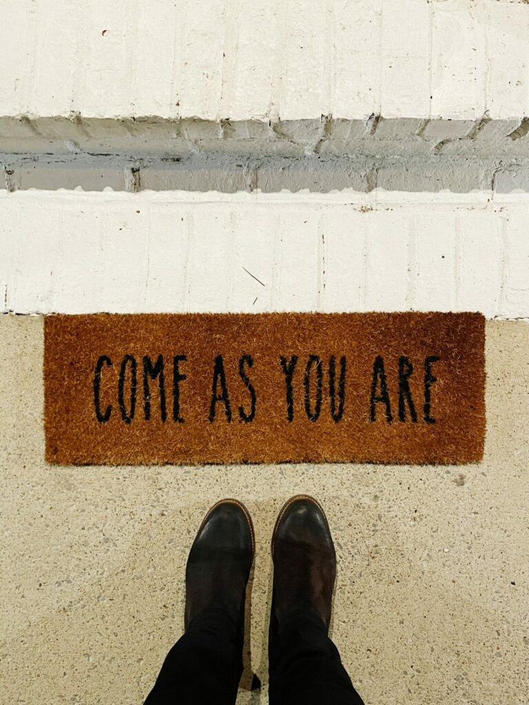 black shows standing by rug that says come as you are