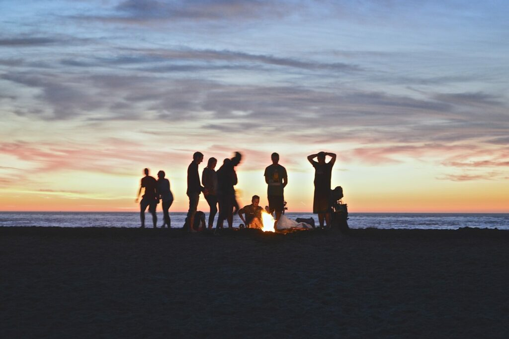 group of people at beach around a fire