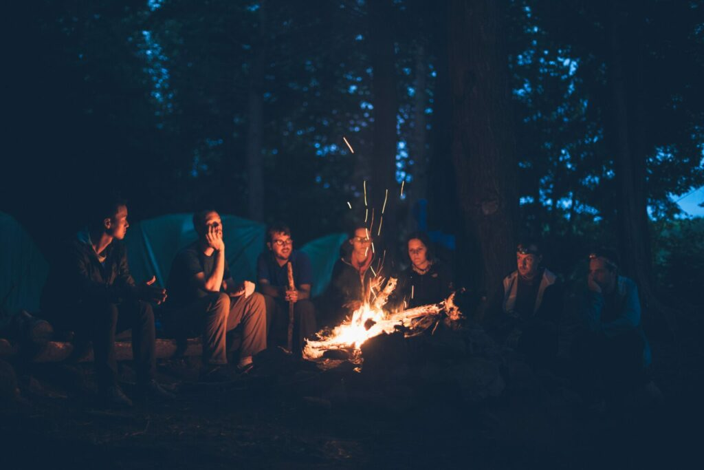 group of people around campfire in woods