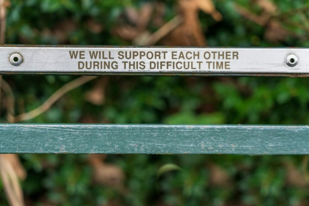 """bench with top piece that says """"we will support ecah other during this difficult time"""""""