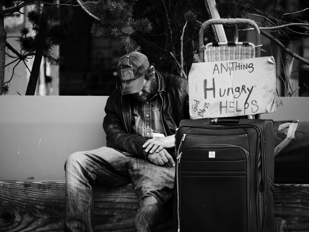 homeless man with a sign on a quitcase that says hungry anything helps